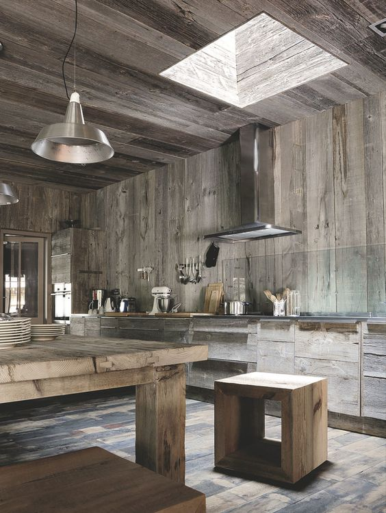 a contemporary chalet kitchen with reclaimed wooden walls and cabinets, with matching furniture and stainless steel appliances