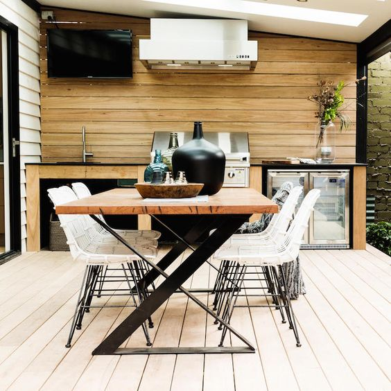 a contemporary dining area with a catchy zigzag leg table, white rattan chairs and a grill next to it