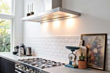 a contemporary kitchen with black cabients, a white subway tile backsplash and concrete countertops