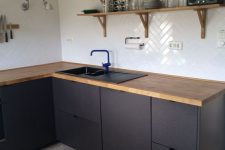 a contemporary matte black kitchen with light stained wooden countertops and matching wooden shelves looks chic