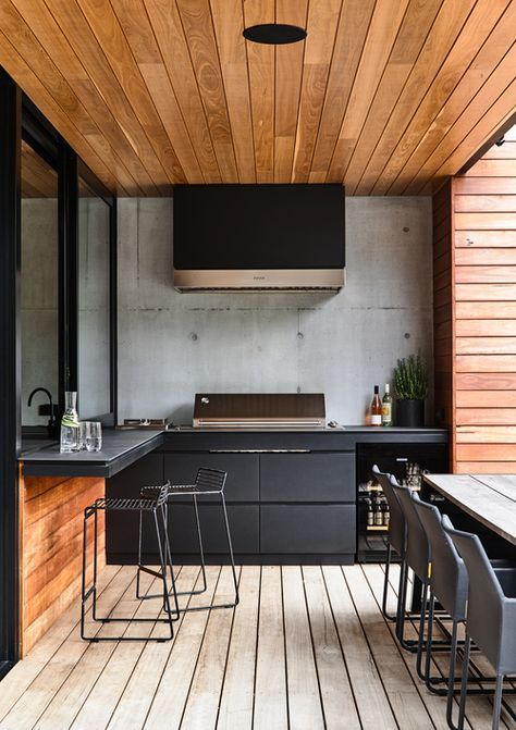 a contemporary outdoor barbecue area done in black and stained wood, with matte cabinets, a grill, a hood and some meal spaces