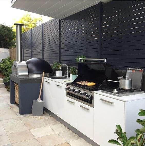 a contemporary outdoor barbecue area done in black and white, with a pizza oven and a grill plus storage cabinets