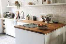 a contemporary sleek white kitchen with light stained wooden countertops and a white subway tile backsplash for a catchier look