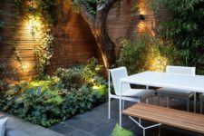 a contemporary townhouse garden with stone tiles, minimalist furniture of wood and metal, lush textural greenery and a tree growing