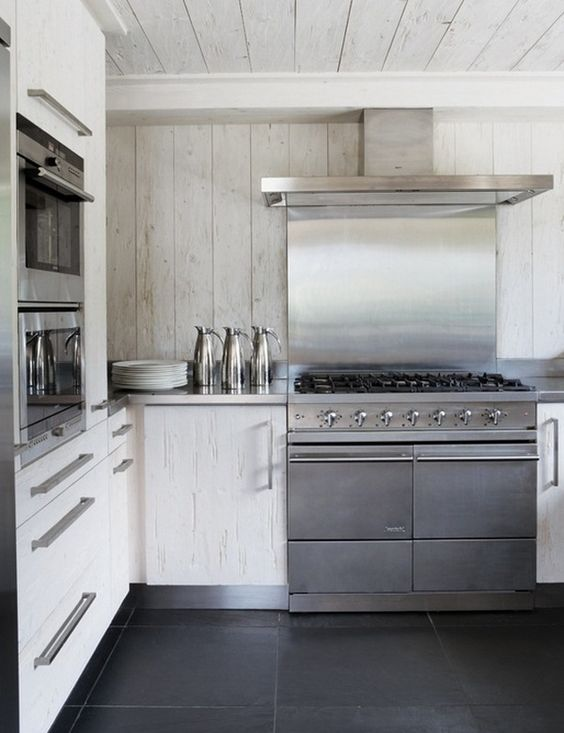 a contemporary white chalet kitchen all clad with wood, with stainless steel appliances is laconic and chic