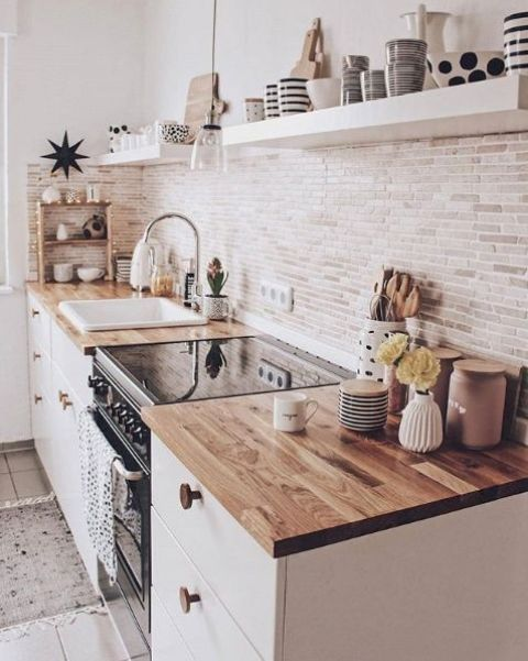 a contemporary white kitchen with light stained butcherblock countertops, a pendant lamp and white floating shelves