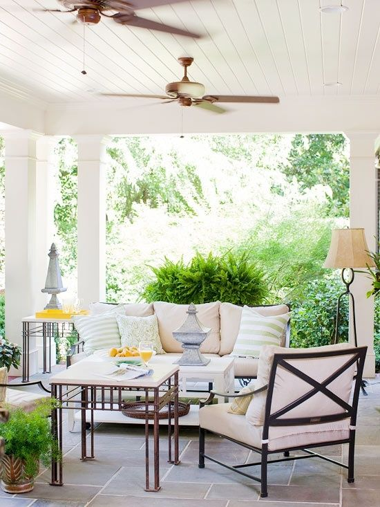 a cozy summer porch with ceiling fans, comfy upholstered furniture, a floor lamp and some tables