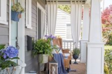a cozy summer porch with wicker futniture, potted greenery and flowers, a jute rug, a dresser and some curtains