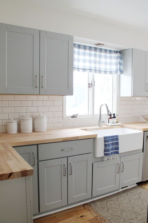 a cozy welcoming dove grey kitchen with light stained butcherblock countertops and touches of plaid