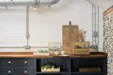 a dark grey kitchen with light stained wooden countertops that match wooden beams and make the space look more refined