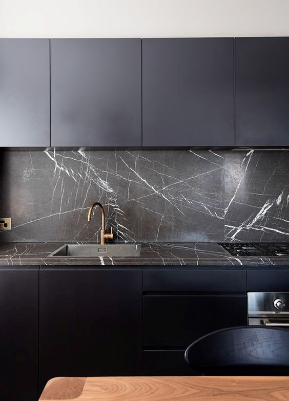 a dark stone countertop plus a matching backsplash make this midnight blue kitchen stunning