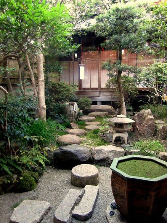 a fantastic Japanese backyard with rocks, a stone lantern, greenery and trees and a bowl with greenery inside
