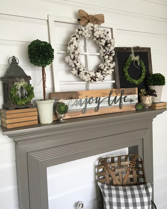 a farmhouse mantel with a pallet, a cotton wreath, greenery wreaths and greenery in planters
