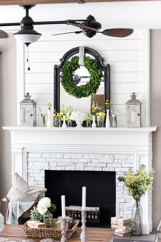 a farmhouse mantel with candle lanterns, vases with bright blooms, a greenery wreath and a mirror