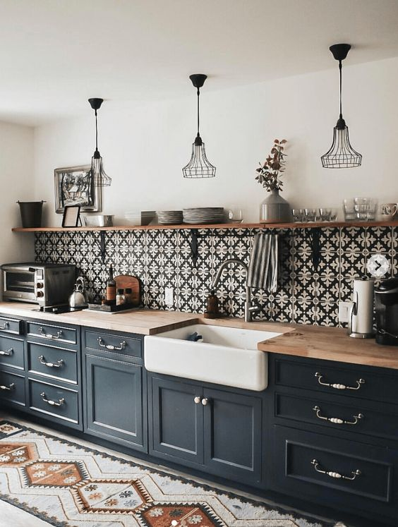 a graphite grey farmhouse kitchen with only lower cabinets and light stained countertops and a long open shelf over them