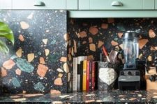 a green kitchen with bold terrazzo countertops and a backsplash is a fun and bold idea to add drama to the space