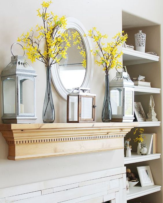 a laconic vintage summer mantel with blooming branches, candle lanterns and a mirror