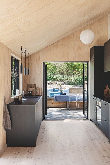 a light-colored chalet kitchen clad with wood and plywood, with black cabinets and stylish pendant lamps