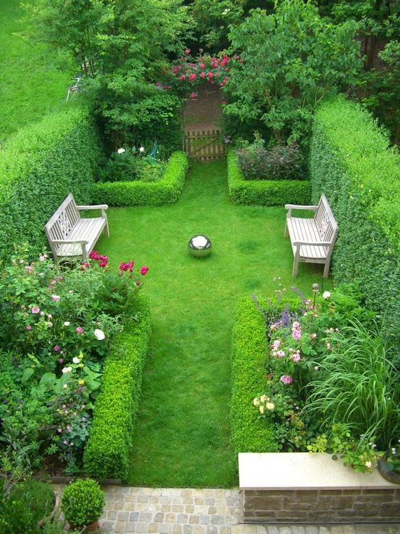 a lush townhouse garden with much greenery, living walls framing the flower beds, wooden benches and some stone