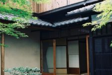 a mini Japanese courtyard with pebbles, rocks, greenery, a tiny tree and a stone bowl with water is very cool