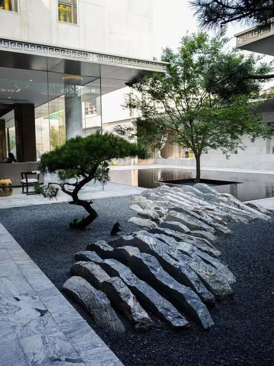 a minimalist Japanese courtyard with a rock that seems to be sliced, two low trees and a sleek pond around one of them