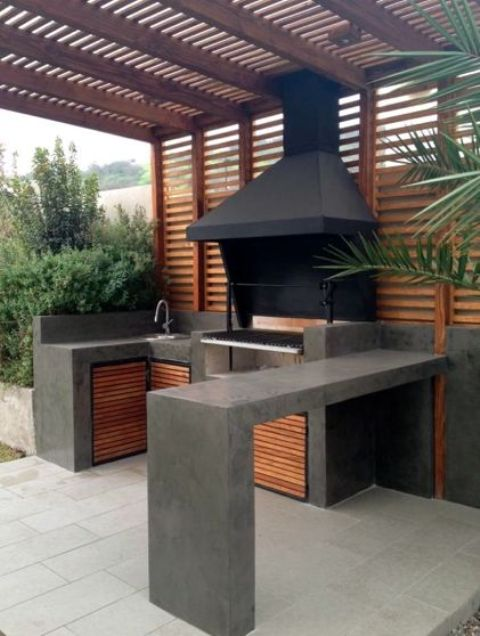 a minimalist bbq area of dark concrete and wood, with a grill and a sink plus a concrete countertop for eating