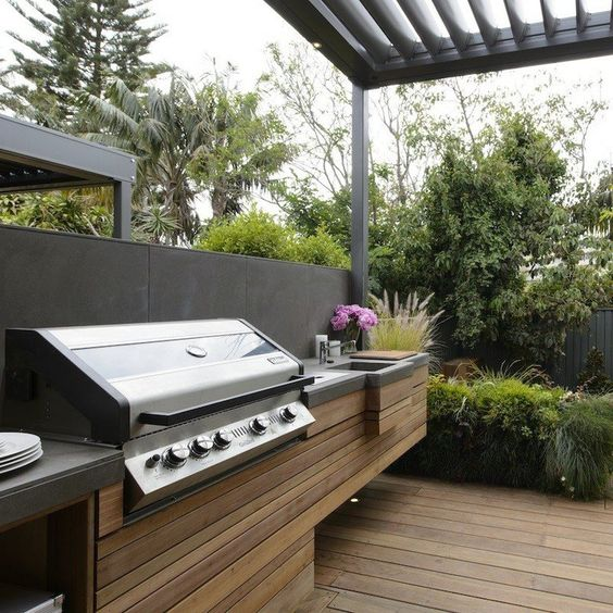 a minimalist bbq area of wooden planks and a concrete countertop plus a grill