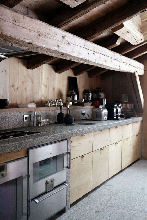 a minimalist chalet kitchen done with wooden beams, sleek wooden cabinets, grey countertops and metal appliances