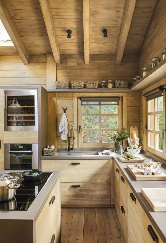 a minimalist chalet kitchen fully done with light-colored wood, with concrete countertops and wooden beams on the ceiling