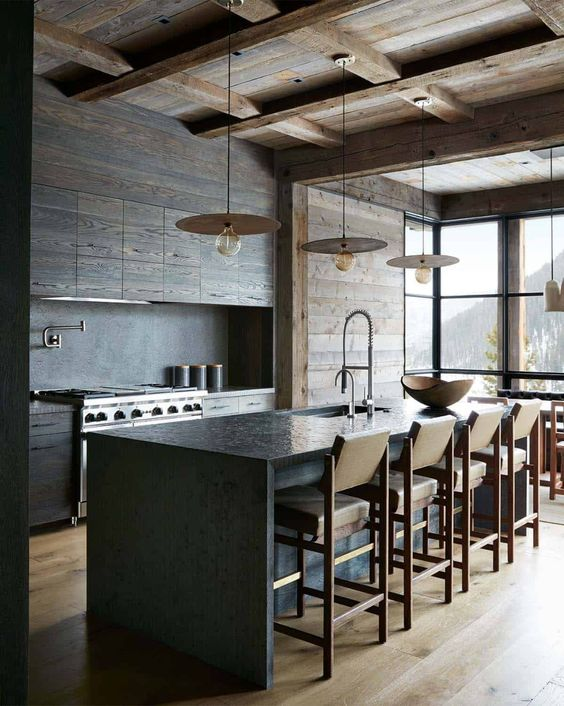a minimalist chalet kitchen with sleek wooden cabinets and a wooden ceiling and walls, a stone kitchen island and leather chairs