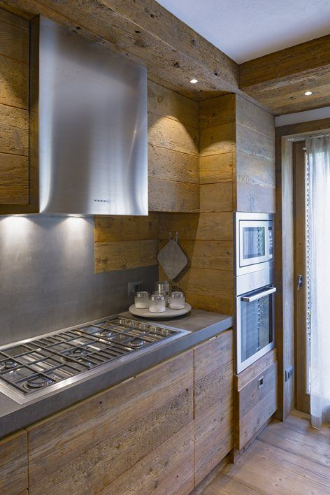 a minimalist chalet kitchen with sleek wooden cabinets and walls, concrete countertops and staineless steel appliances