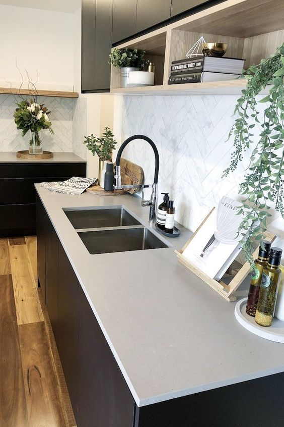 a minimalist kitchen with black cabinets, concrete countertops and a white marble tile backsplash