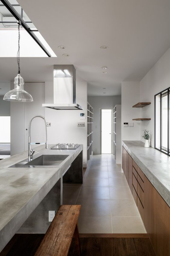 a minimalist kitchen with sleek wooden cabinets and a concrete countertop plus a concrete kitchen island