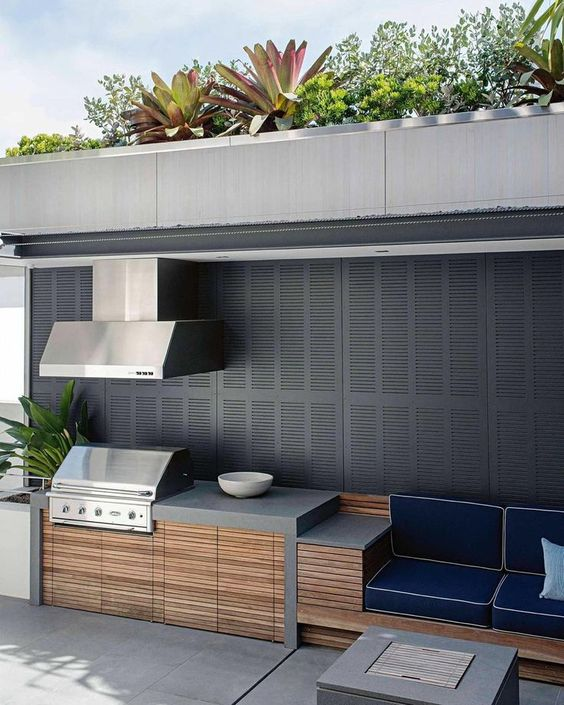 a minimalist outdoor bbq area of concrete, wood and metal with a cooking zone, a grill with a hood and a sitting zone