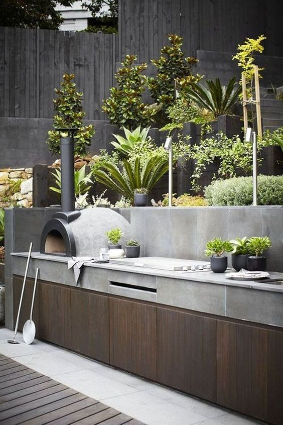 a minimalist outdoor bbq area of wood and concrete, with a grill and a pizza oven plus potted greenery