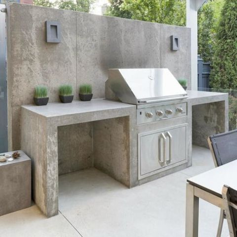 a minimalist outdoor grill zone of concrete, with a grill and potted greenery to refresh the space