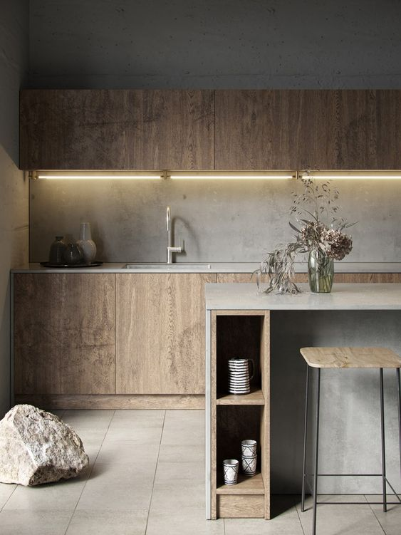 a minimalist plywood kitchen with sleek cabinets, a concrete backsplash and countertops plus a concrete kitchen island