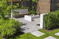 a minimalist townhouse garden with a lawn, pebbles, tiles, minimalist furniture, much greenery all around