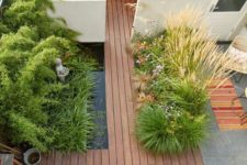 a minimalist townhouse garden with a wooden deck, a pond, planted herbs and grasses and a built-in bench