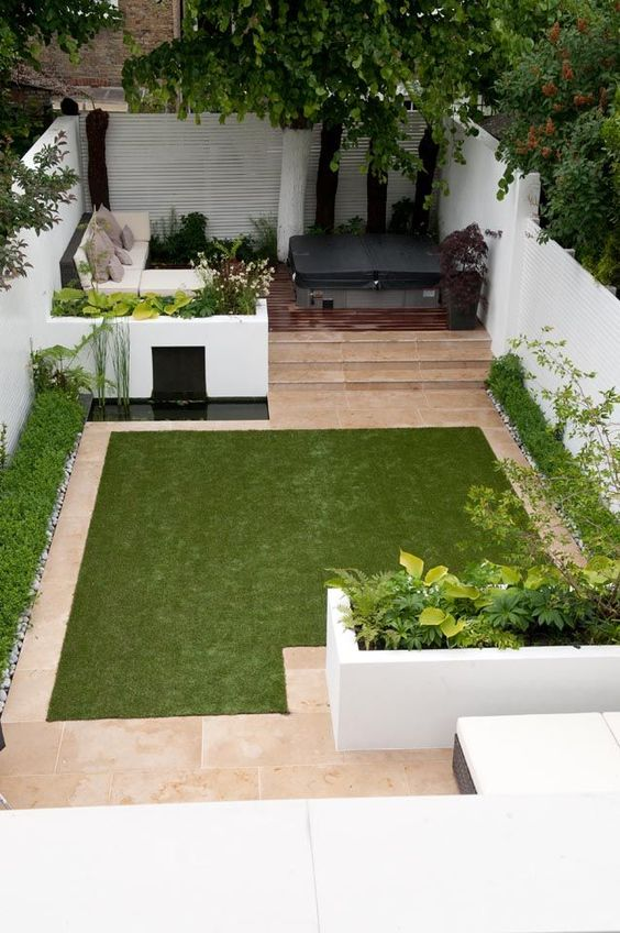 a minimalist townhouse garden with white flower beds with greenery, a tiny pond, a manicured lawn, a sectional sofa and a hot tub