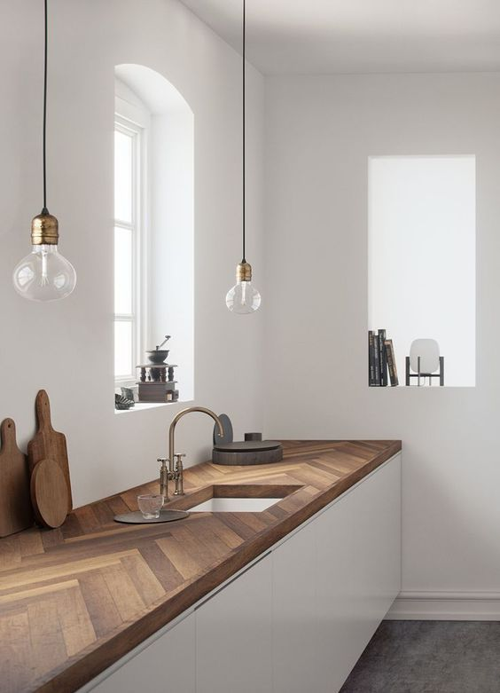 a minimalist white kitchen with dark stained chevron butcherblock countertops and pendant bulbs over the space