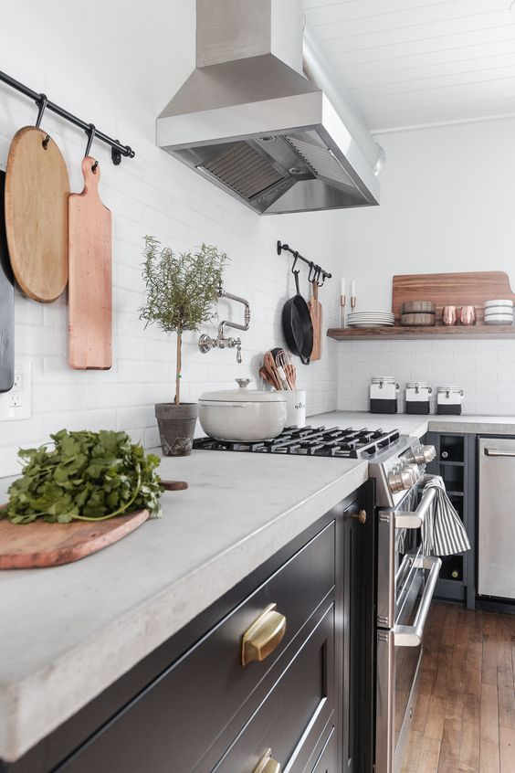 a modern farmhouse kitchen in black, with concrete countertops and stainless steel appliances