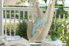 a modern farmhouse porch with a hanging macrame chair, a burlap ottoman, a white side table and greenery