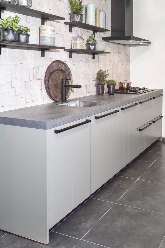 a modern kitchen with grey cabinets, concrete countertops and a catchy backsplash plus dark shelves