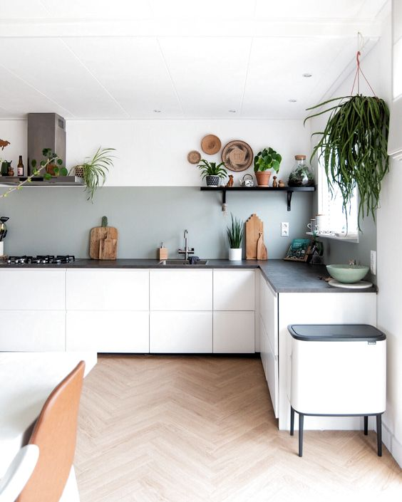a modern kitchen with sleek white cabinets, a black concrete countertops and a grey backsplash plus lots of greenery