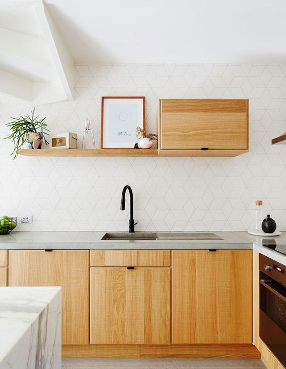 a modern white kitchen with a catchy tile backsplash and light-colored wooden cabients plus concrete countertops