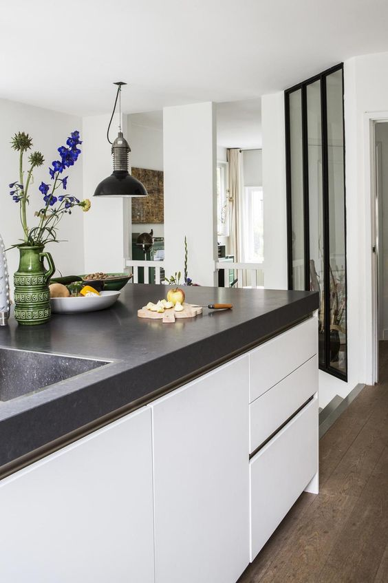 a modern white kitchen with a large kitchen island with a black concrete countertop is veyr welcoming