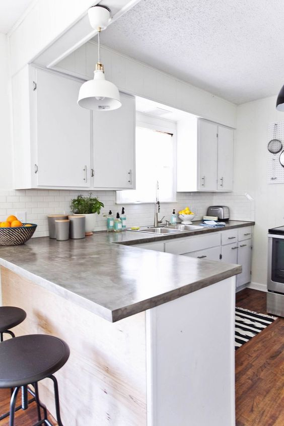 a modern white kitchen with concrete countertops, a white subway tile backsplash and a pendant lamp