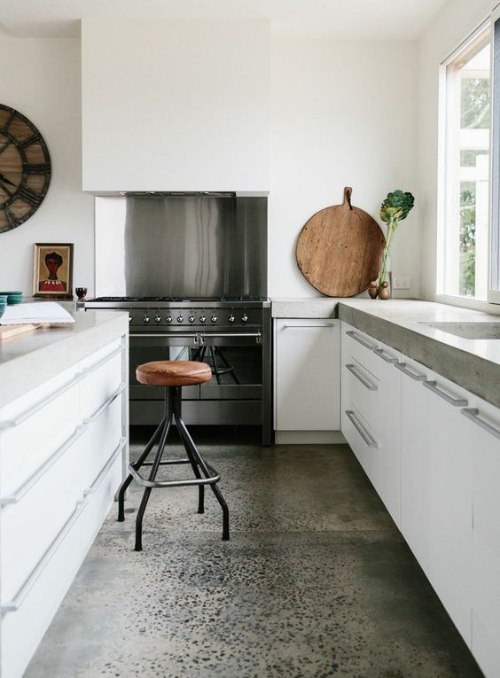 a modern white kitchen with white cabinets, concrete countertops and a large hood