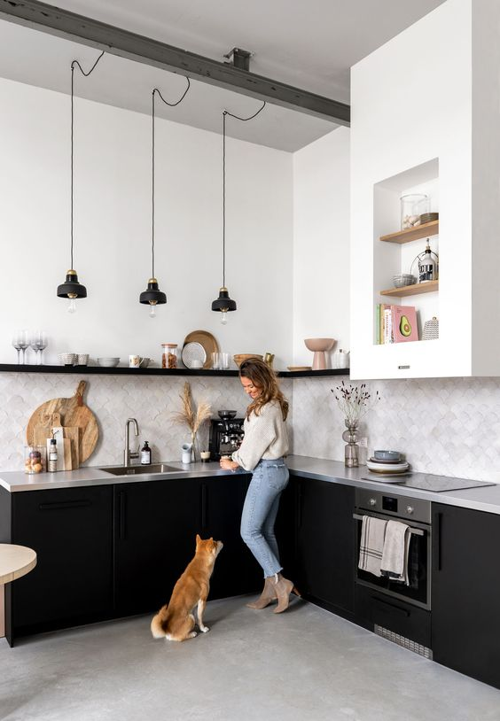 a monochromatic kitchen with black cabinets, a concrete countertop and a grey tile backsplash